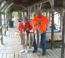 Man and woman with stringer of striped bass on Norfork Lake