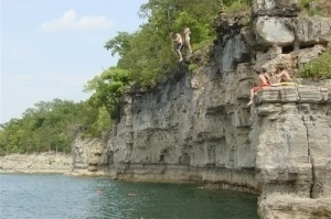 Kids jump into water from cliffs on Norfork Lake