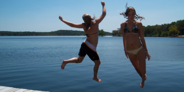 Girls jumping into Norfork Lake