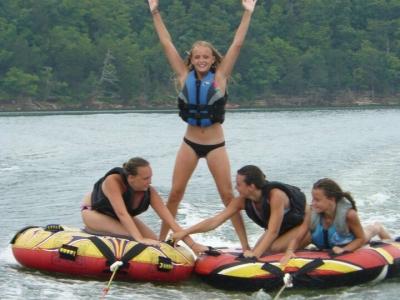Girls do tricks while tubing on lake