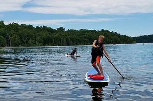 Boy paddleboarding on Norfork Lake