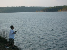 Man fishing on shore Norfork Lake